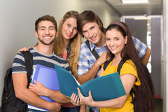 Students holding folders at college corridor. Portrait of happy students holding folders at college corridor Royalty Free Stock Images
