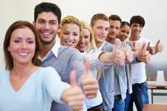 Students holding thumbs up. Many happy successful students holding their thumbs up Stock Images