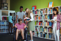 Students interacting with each other in library. At school Royalty Free Stock Photo