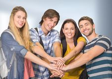 Students joing hands together in front of blurred background Royalty Free Stock Photography