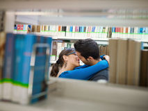 Students kissing in library. Two caucasina students hugging and kissing behind shelves in library. Horizontal shape, side view, copy space Royalty Free Stock Photography