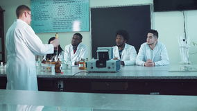 Students in laboratory. Students looking at the experiment in the laboratory stock video