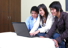 Students on a laptop. Group of students on a laptop over a bed Royalty Free Stock Image