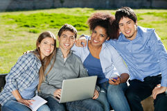 Students With Laptop And Book Sitting In College. Portrait of happy young students with laptop and book sitting in college campus Stock Photo