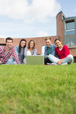 Students with laptop in the lawn against college building Royalty Free Stock Photography