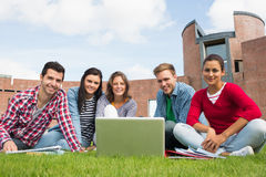 Students with laptop in the lawn against college building Stock Image