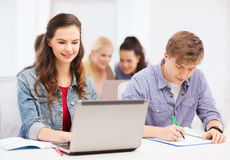 Students with laptop and notebooks at school Royalty Free Stock Image