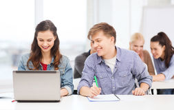 Students with laptop and notebooks at school Royalty Free Stock Photos