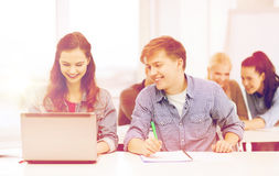 Students with laptop and notebooks at school Royalty Free Stock Images