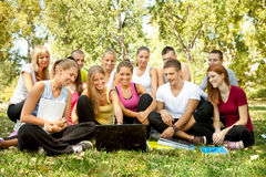 Students with laptop in park. Group of students with laptop in park, looking in laptop Royalty Free Stock Photography