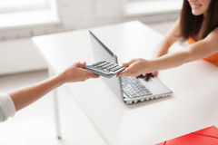 Students with laptop sharing calculator at school Royalty Free Stock Photography