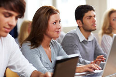 Students with laptops in class. Happy students with their laptops in university class Royalty Free Stock Photos