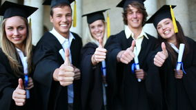 Students laughing while holding their diplomas stock footage