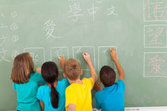 Students learning chinese. Rear view of elementary school students learning chinese writing on chalkboard royalty free stock photos