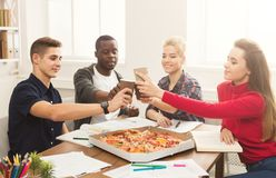 Students learning and eating pizza. Happy people eating pizza and cheering with paper cups at coworking office during break. Food delivery and team work concept Royalty Free Stock Images