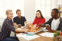 Students learning and eating pizza. Pizza delivery. Happy people eating lunch at coworking office during break. Fast food and team work concept Stock Photos