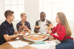 Students learning and eating pizza. Pizza delivery. Happy people eating lunch at coworking office during break. Fast food and team work concept Royalty Free Stock Photo