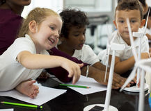 Students learning energy producer from sola. Diverse kindergarten students learning energy producer from solar windmill in science class stock image