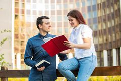 Students learning for exam together in a city park. Smiling students learning for exam together in a city park. Students Brainstorming Meeting learning for exam royalty free stock photography