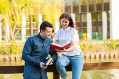 Students learning for exam together in a city park. Smiling students learning for exam together in a city park. Students Brainstorming Meeting learning for exam royalty free stock images