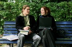 Students learning outside. Two students chatting on a bench. Young man with a notepad, books and pen, woman with a laptop Stock Photography