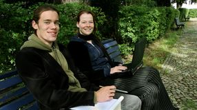 Students learning outside. Two students on a bench looking into the camera. Young man with a notepad, books and pen, woman with a laptop Royalty Free Stock Photos