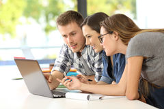 Students learning together on line in a classroom. Three students learning together on line with a laptop in a classroom Stock Images