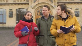 Students leaves the university. Students walks from the university. Friends are discussing some educational material. Three young people talks with eachother stock video footage