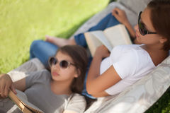 Students leisure time, young girls reading and relax outdoors. Best friends spending tine together in summer day. Wearing sunglasses, smilimg, reading. Doing Royalty Free Stock Images