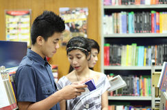 Students in the library. Group of asian students looking for books in the library Stock Image