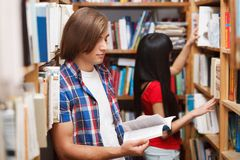 Students in a library. Choosing a book Stock Photos