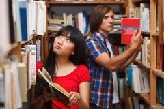 Students in a library. Choosing a book Royalty Free Stock Photography