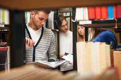 Students in library. Choosing books Stock Photos