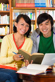 Students in library are a learning group. Students - Young Asian women and men in library with laptop and book learn, they are a learning group Royalty Free Stock Images