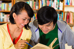 Students in library are a learning group. Students - Young Asian women and men in library with laptop and book learn, they are a learning group Stock Image