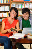 Students in library are a learning group. Students - Young women and men in library with laptop and book learn, they are a learning group Royalty Free Stock Photography