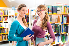 Students in library are a learning group. Students - Young women in library with books in a learning group Stock Images