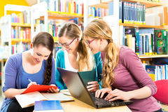 Students in library are a learning group. Students - Young women in library with laptop and book learning in group Royalty Free Stock Image