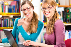 Students in library are a learning group. Students - Young women in library with laptop and book learning in group Royalty Free Stock Images