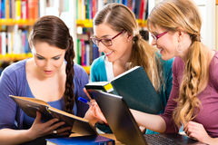 Students in library are a learning group. Students - Young women in library with laptop and book learning in group Royalty Free Stock Photo