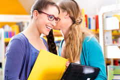 Students in library are a learning group. Students - Young women in library with laptop and book learning in group Royalty Free Stock Photos