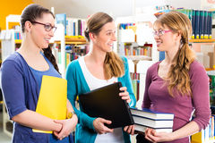 Students in library are a learning group. Students - Young women in library with laptop and book learning in group Royalty Free Stock Photography