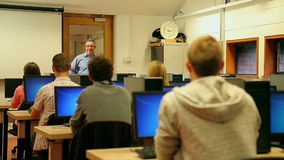 Students listening to lecturer in computer room stock video footage