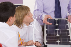 Students listening to teacher explaining solar panel and wind turbines in classroom Stock Photo
