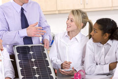Students listening to teacher explaining solar panel and wind turbines in classroom Royalty Free Stock Images