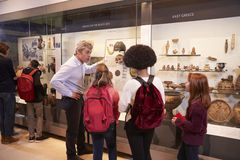 Students Looking At Artifacts In Case On Trip To Museum Royalty Free Stock Image