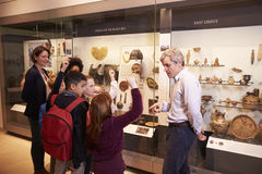Students Looking At Artifacts In Case On Trip To Museum Stock Photo