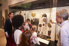 Students Looking At Artifacts In Case On Trip To Museum Royalty Free Stock Photography