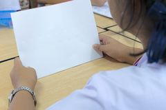 Students are looking at blank white paper. royalty free stock photo
