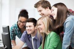 Students looking at computer monitor at school Stock Photo